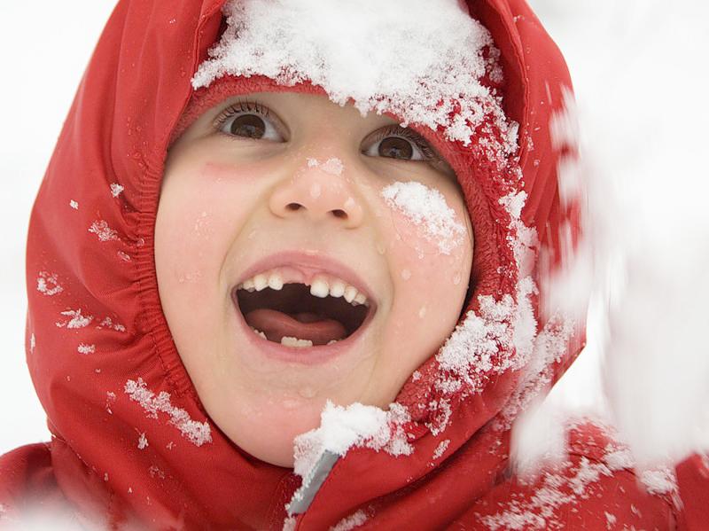 ребёнок в снегу улыбается